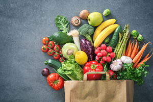 fresh fruits and veggies spilling out of grocery bag